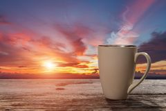 Hot drink on wood table. In sunrise golden sky Stock Images
