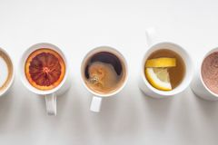 Several different hot drinks on the white table - coffee shop menu. Hot drinks coffee and tea in white cups stand in a line on a white table. Top view, flat lay royalty free stock image