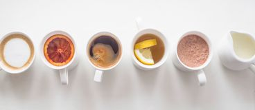 Several different hot drinks on the white table - coffee shop menu. Hot drinks coffee and tea in white cups stand in a line on a white table. Top view, flat lay royalty free stock photo