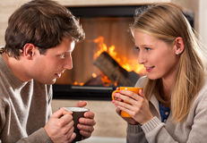 Hot drinks and fireplace. A couple warming up with hot drinks by a fireplace Royalty Free Stock Photography