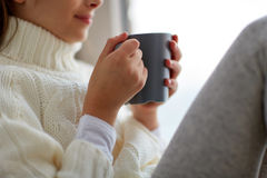 Girl with tea mug sitting at home window. Hot drinks and people concept - beautiful girl in winter sweater with tea mug sitting at home window Stock Images