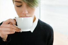 Hot drink girl tasting coffee tea cup beverage. Hot drinks. young girl tasting coffee or tea from a white cup. cafe or restaurant beverage service concept Royalty Free Stock Image