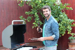 Hot dude cooking meat on the barbecue grill.  Stock Photo