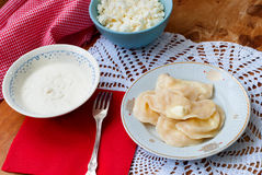 Hot dumplings with cottage cheese with sour cream and butter on a plate. Delicious hot dumplings with cottage cheese poured melted butter and sour cream, bowl Stock Photo