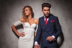 Hot elegant couple holding hands and posing in studio Stock Photography