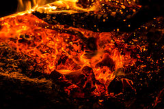 Hot embers and fire. Close-up on a camp fire.  We can see the bright  sparkles of the hot embers Royalty Free Stock Images