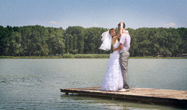 Hot embrace. The groom holds the bride on hands. A happy newly-married couple on river jetty Stock Images