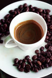 Hot espresso. Coffee in white cup and disk with coffee bean stock image