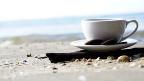 Hot espresso coffee on the beach. A cup of espresso coffee on the beach with cookies Royalty Free Stock Photography