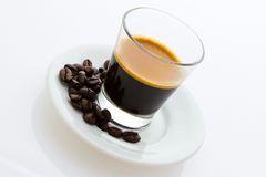 Hot espresso coffee with coffee beans. Hot espresso coffee with roasted coffee beans on a small plate Royalty Free Stock Image