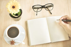 Hot espresso in coffee shop. Hot espresso and book with pen on wood table Stock Photography
