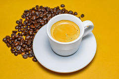 Hot espresso cup with coffee beans. Hot espresso cup with coffee beans on brown background Stock Photography