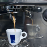 Hot espresso in cup on coffee machine Stock Images