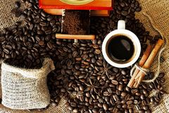 Hot espresso in flavored coffee beans and cinnamon Royalty Free Stock Images