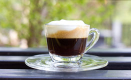 Hot  espresso with milk and foam in cup. Royalty Free Stock Photo