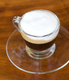 Hot  espresso with milk and foam in cup. Royalty Free Stock Image