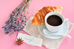 Hot espresso on wood table. Hot espresso and croissant with lavender flower on wood table Stock Photo