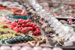 Hot of expensive gemstone jewelry. Rings, necklaces and bracelets made of peridot and azurite stones, red coral, sapphire, rose qu. Shot of expensive gemstone Stock Images