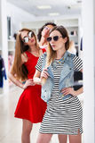 Hot fashionable young women wearing glasses posing looking in mirror standing in womenswear boutique.  Stock Photo