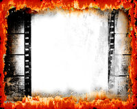 Hot Film Grunge Background. Fire orange grunge layers border on film strips with copy space in the middle for metaphor of a hot film Stock Image
