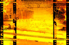 Hot film grunge background. Fiery orange and yellow grunge background is from a photograph, then layered with film strips border Royalty Free Stock Photography