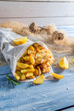 Hot fish cod with chips in newspaper with lemon Royalty Free Stock Image