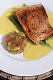 Hot Fish dish 3; close crop. Pan fried or sauteed salmon fillet on asparagus and lemon butter sauce, served with avocado, tomato and onion salsa. Flesh side up Royalty Free Stock Images
