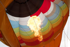Hot flame up the inside of a colorful hot air balloon Royalty Free Stock Image