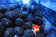 Hot flaming charcoal briquettes glowing in the barbeque grill pi. T. Real burning coals before cooking barbecue meat. Black charcoal background for bbq food royalty free stock photography