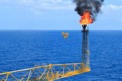 Hot flare boom and fire on offshore production platform Stock Photo
