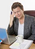 Hot Flash and Headache. Mature businesswoman at her desk having a hot flash and a headache, looking at camera, very distressed Stock Photography