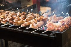 Hot food at the festival of street fast food, sausages, hot dog, fried meat. Hot grilled food at the festival of street fast food, sausages, hot dog, fried meat Royalty Free Stock Images