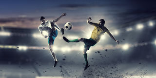 Hot football moments. Football players at stadium field fighting for ball Stock Photos