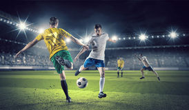 Hot football moments. Football players at stadium field fighting for ball Stock Image
