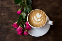 Hot, fragrant coffee in a white cup with foam in the form of a heart stands on a dark wooden background beside lies a. A fresh morning cappuccino in a white cup stock photos