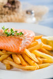Hot french fries with salmon served on plate with lemon Royalty Free Stock Image