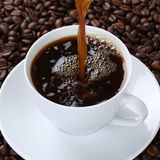 Hot fresh coffee pouring in cup Royalty Free Stock Photos