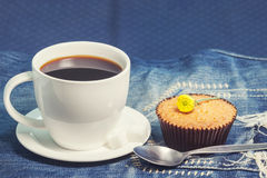 Hot fresh coffee in white cup and soft cake on blue jeans on tab Stock Image