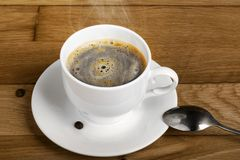 Hot fresh coffee in a white cup with spoon Royalty Free Stock Photo