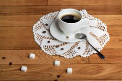 Hot fresh coffee in white cup with sugar on wooden table Royalty Free Stock Photography