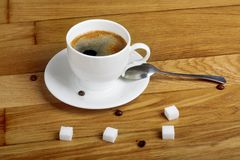 Hot fresh coffee in white cup with sugar on wooden table Stock Photography