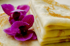 Hot fried pancakes. Fresh hot blinis with violet flowers close up Royalty Free Stock Photography