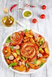 Hot fried sausages and potato on platter. Bavarian sausages - round fried spiral sausages on white dish with potato wedges, pieces of chili and basil leaves, on royalty free stock images