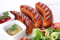 Hot and fried sausages with vegetables and spices Stock Photos