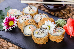 Hot fried Sushi rolls and maki set with Crab Meat, cream cheese, avocado and wasabi on black stone on bamboo mat, selective focus. Royalty Free Stock Image