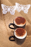 Hot frothy drink cappuccino chokolate dusted. White paper butterfly, shallow dof Royalty Free Stock Image