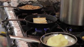 In a hot frying pan the cook fries flour envelopes with a filling. stock video footage