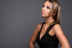 Hot girl. Blond model in black dress posing on grey background Stock Image