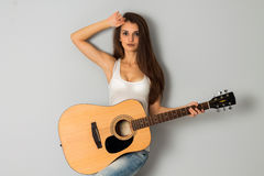 Hot girl with guitar in hands. Looking at the camera in studio on grey background royalty free stock photo