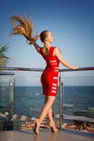 A hot girl on a natural background. An elegant lady on a hotel terrace in summer. A girl in a red dress is looking at the sea. An extremely attractive young Royalty Free Stock Image